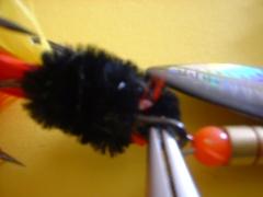 Abb. 5: Am Schluß, den Plüschdraht wieder von unten nach oben zur Öse biegen und durchziehen. Noch ein bis zweimal umwickeln, dann kappen.